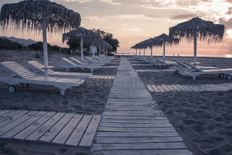 La vista lunatica del mare e della spiaggia con i parasoli a colore del chillout del tramonto ha spaccato la tonalità fotografie stock libere da diritti