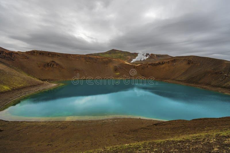 La vista nel cratere di Krafla e nel lago vulcanici Viti in Islanda del Nord, vapore dell'unità della centrale elettrica di energ fotografie stock