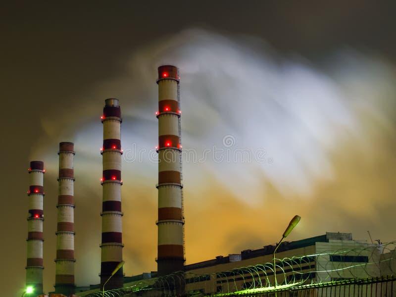 La vista nocturna de los tubos de centrales térmico, emitiendo humo, destacó de debajo por el contraluz imágenes de archivo libres de regalías