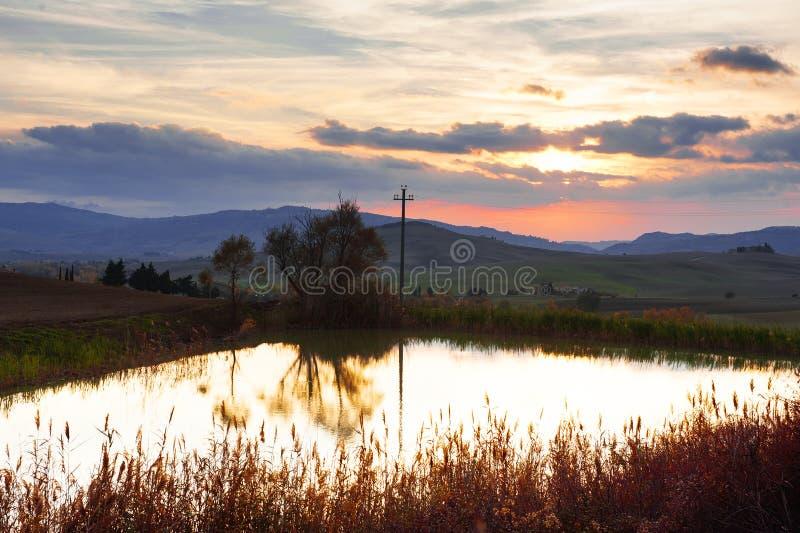 La vista panorámica de una pequeña charca, Rolling Hills, el cielo y las nubes en la puesta del sol en campo toscano ajardinan, T imagen de archivo libre de regalías