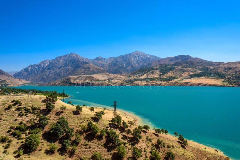 La vista panoramica del lago Charvak, un lago-bacino idrico artificiale enorme ha creato erigendo un'alta diga di pietra sul fium immagini stock