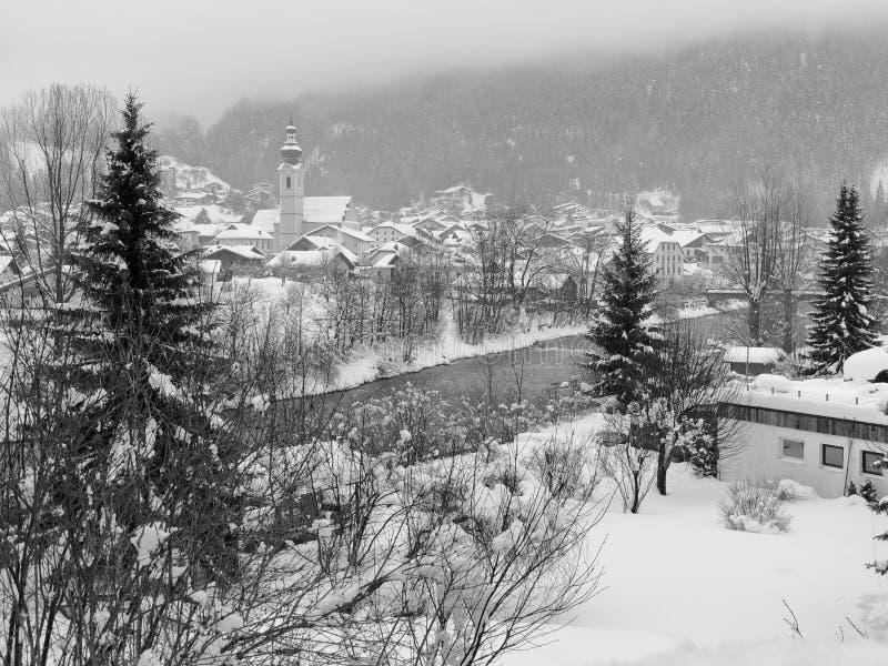 La vista panoramica di cattivo fiume della locanda attraversa il villaggio nevoso di Pfunds, Tirolo, Austria fotografia stock