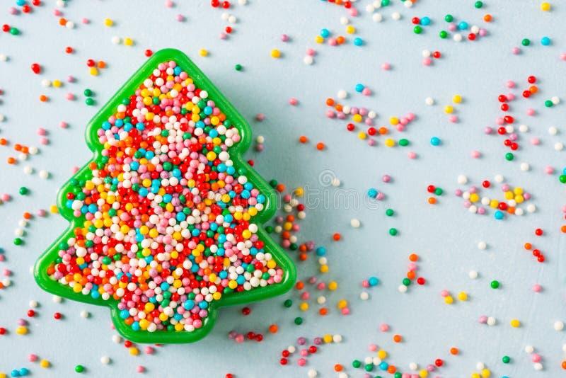 La vista posta piana della taglierina a forma di del biscotto dell'albero di Natale riempita di zucchero dell'arcobaleno spruzza fotografie stock libere da diritti