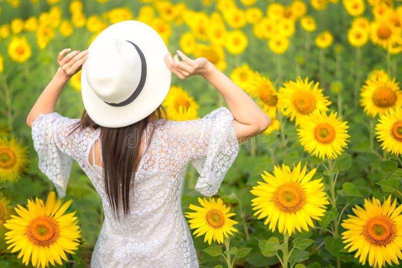 La vista posterior de las mujeres de la forma de vida del viaje con las manos sube el sombrero en campo del girasol, en día de ve fotografía de archivo