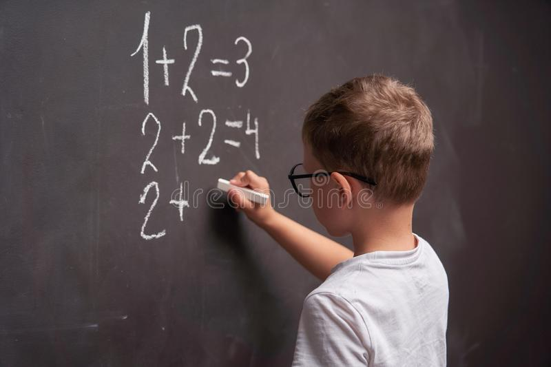 La vista posterior de un colegial soluciona un ejemplo matemático en una pizarra en una clase de la matemáticas foto de archivo
