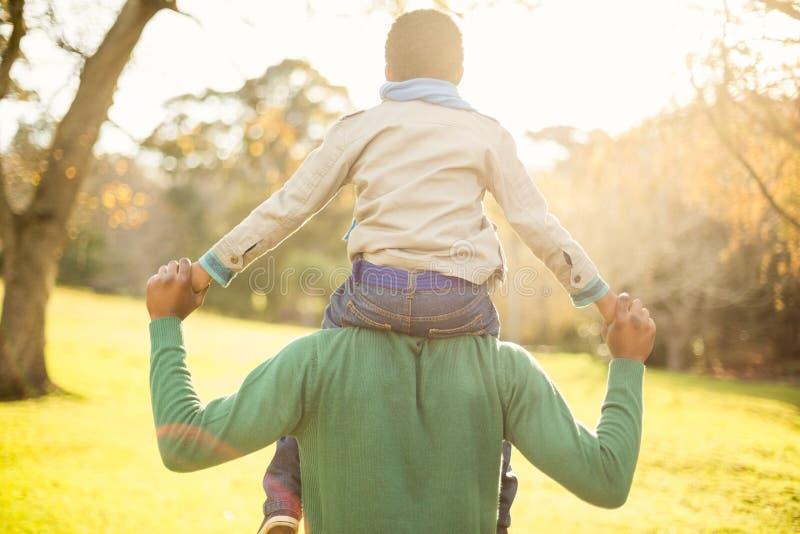 La vista posterior de un padre con su hijo adentro lleva a cuestas foto de archivo