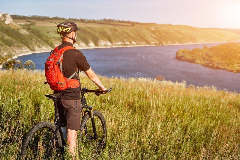 La vista posterior del ciclista joven se coloca con la bici de montaña en el prado verde sobre el río grande fotografía de archivo