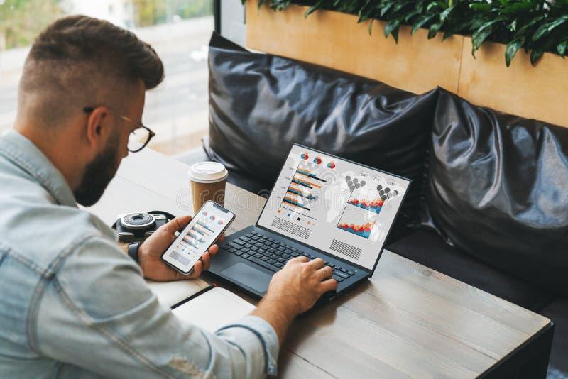 La vista posterior del inconformista del hombre de negocios en vidrios se está sentando en la tabla, trabajando en el ordenador p fotografía de archivo libre de regalías
