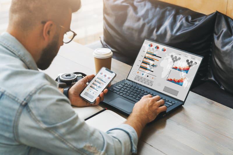 La vista posterior del inconformista del hombre de negocios en vidrios se está sentando en la tabla, trabajando en el ordenador p fotos de archivo libres de regalías
