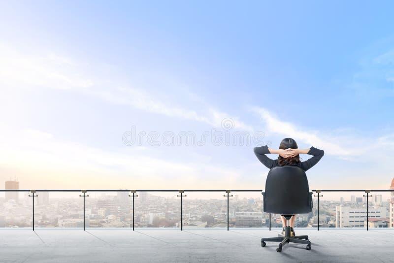 La vista posterior la mujer de negocios asiática que se sienta en la silla de la oficina en terraza moderna se relaja y que mira  imagenes de archivo