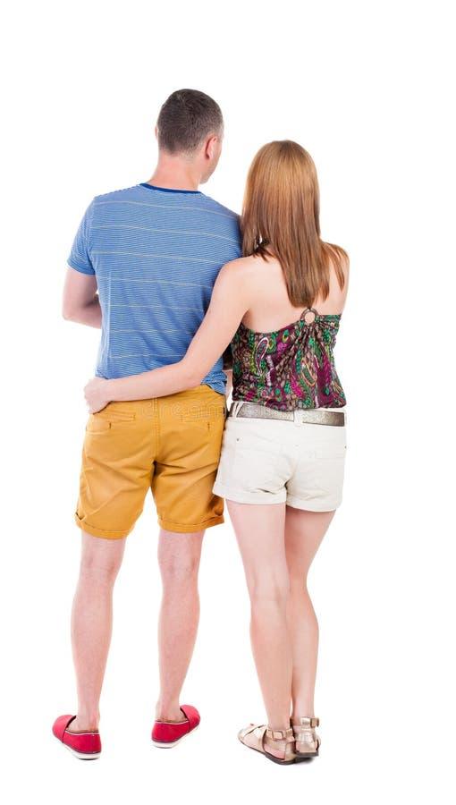 La vista posteriore dei giovani che abbracciano le coppie in breve abbraccia e guarda immagini stock libere da diritti