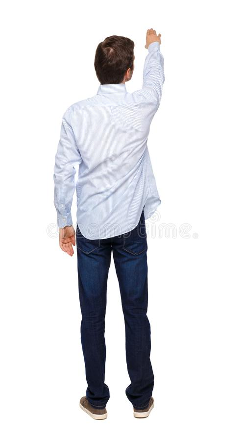 La vista posteriore di un uomo in jeans punta la mano verso l'alto fotografia stock libera da diritti