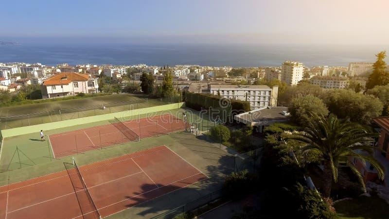La vista a?rea de la corte de la ciudad y del lujo, gente que juega al tenis, afici?n y se relaja fotos de archivo libres de regalías