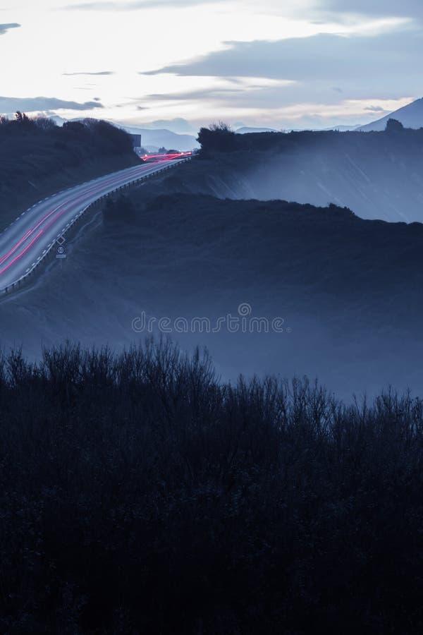 La vista scenica del paesaggio nella penombra sulla strada costiera con l'automobile di traffico si accende sulla linea costiera  fotografie stock libere da diritti