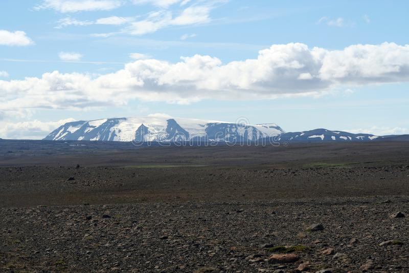 La vista sopra l'ampio terreno incolto sterile nero senza fine nero con neve ha ricoperto le montagne - Islanda fotografie stock