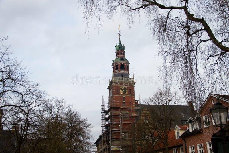La vista su una chiesa ed il suo campanile circondato dagli alberi nella città leer nel Nord della Germania fotografia stock libera da diritti
