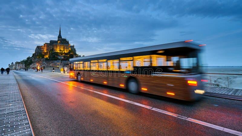 La vista sull'isola famosa di Mont Saint Michel con moto ha offuscato il bus di navetta progettato per il trasporto dei turisti fotografia stock libera da diritti