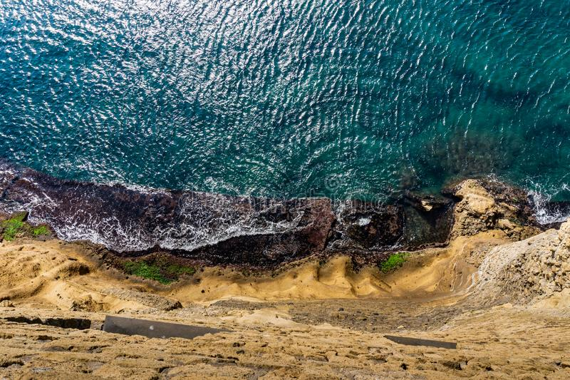 La vista superior aérea del mar agita golpeando rocas en la playa con la agua de mar de la turquesa foto de archivo