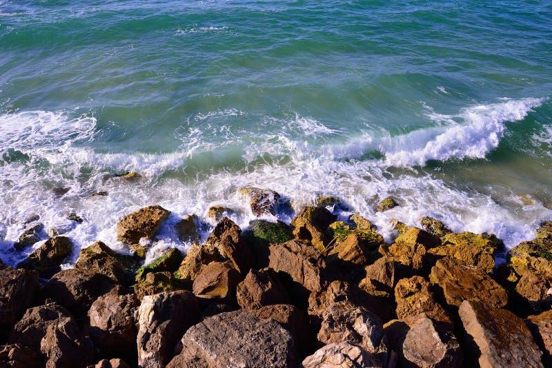 La vista superior aérea del mar agita golpeando rocas en la playa en el teléfono A fotografía de archivo libre de regalías