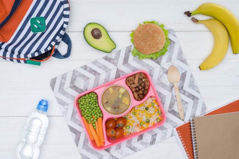 la vista superior de la bandeja con los niños almuerza para la escuela y los cuadernos fotografía de archivo libre de regalías