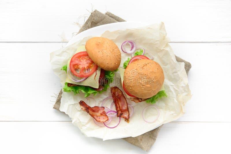 La vista superior de dos hamburguesas sirvió en el papel de la hornada sobre la tabla rústica blanca foto de archivo libre de regalías