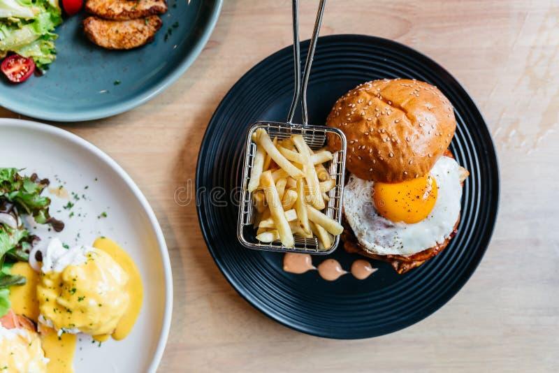 La vista superior de la hamburguesa sabrosa con el huevo frito sirvió con las fritadas en placa negra en la tabla de madera imagenes de archivo