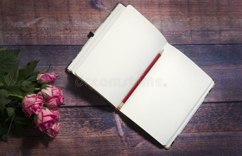 La vista superior de la hoja en blanco del cuaderno y de rosas rojas y rosadas florece en la tabla de madera marrón rústica Copie imagenes de archivo