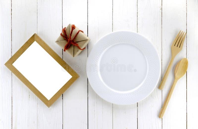 La vista superior de la caja del arte en plato y la cuchara bifurcan en la madera blanca imagen de archivo libre de regalías