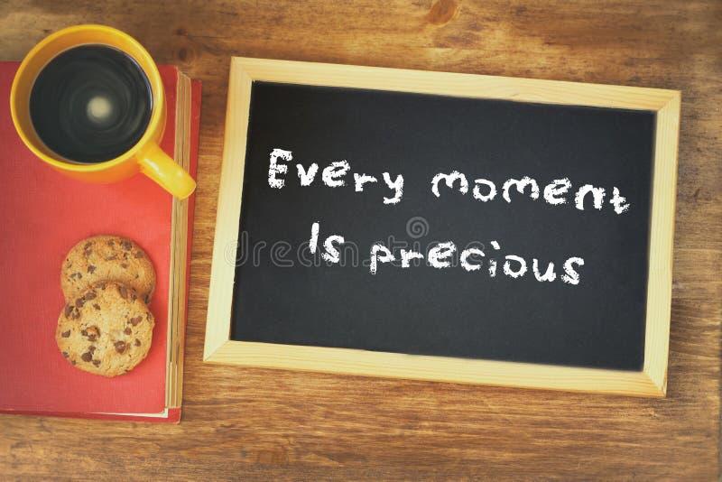 La vista superior de la pizarra con la frase cada momento es preciosa al lado de la taza de café sobre la tabla de madera imagenes de archivo