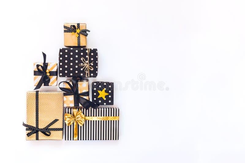 La vista superior de las cajas de regalo en diversos diseños negros, blancos y de oro arregló en forma triangular como el árbol d imagen de archivo
