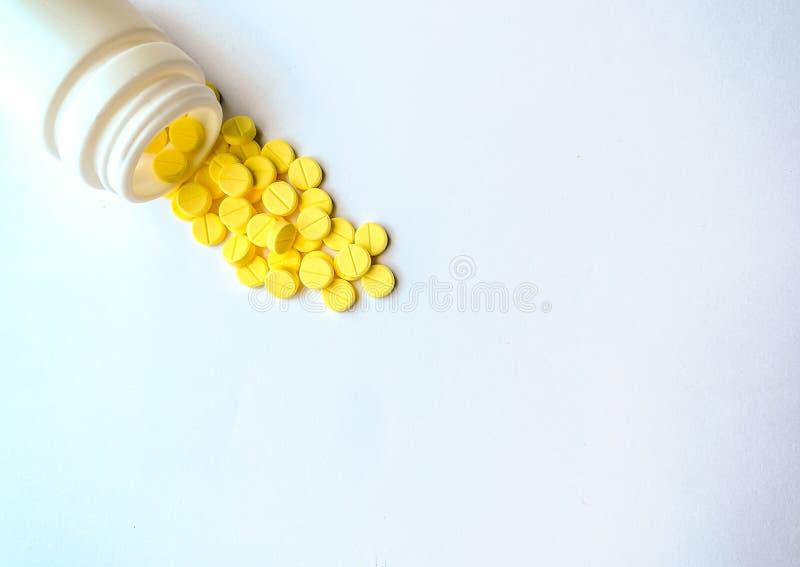 La vista superior de las píldoras de la alergia o Chlorpheniramine vertió de una botella sobre un fondo blanco imágenes de archivo libres de regalías