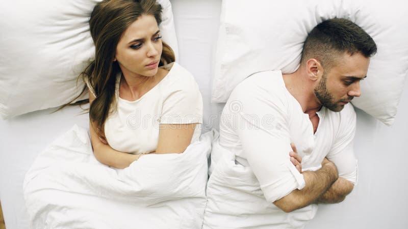 La vista superior de los pares trastornados de los jóvenes que mienten en cama tiene problemas después de pelea y enojados en cas imagen de archivo