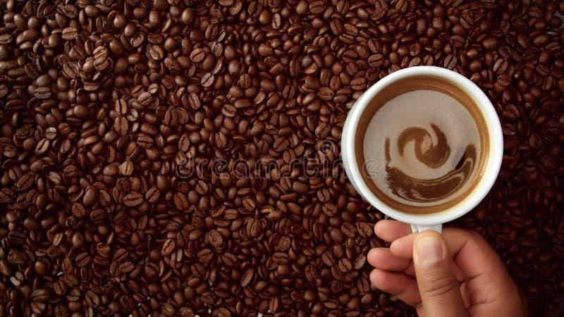 La vista superior de la mano con la taza de coffe negro la puso en fondo de las habas del coffe imagen de archivo libre de regalías