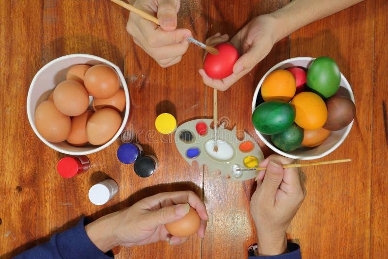 La vista superior de manos de miembros de la familia está coloreando los huevos con una brocha en la tabla de madera para prepara imagen de archivo
