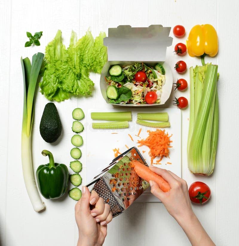 La vista superior de manos prepara la ensalada sana ligera de la cena de la consumición con la zanahoria de los ingredientes foto de archivo libre de regalías
