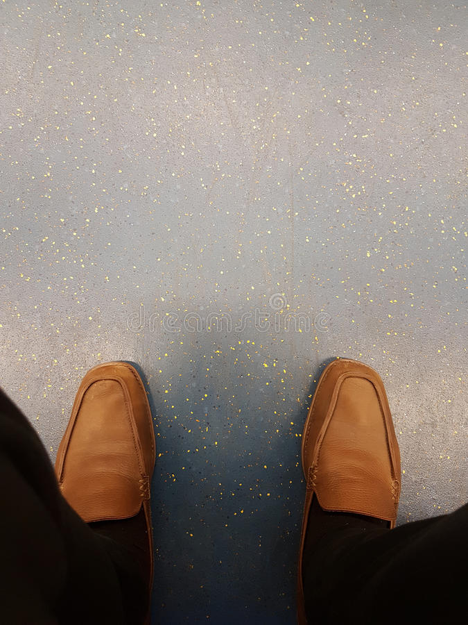 La vista superior de pantalones negros viejos y los zapatos de cuero del marrón amarillo de relajan al hombre de negocios que se  imagenes de archivo