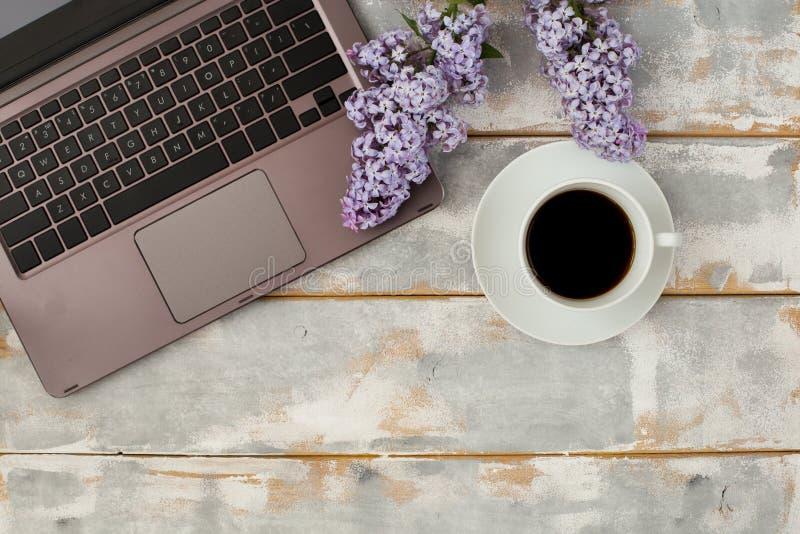 La vista superior de un ordenador y de una taza de café y de lila florece en una tabla de madera blanco-gris Lugar para el texto foto de archivo