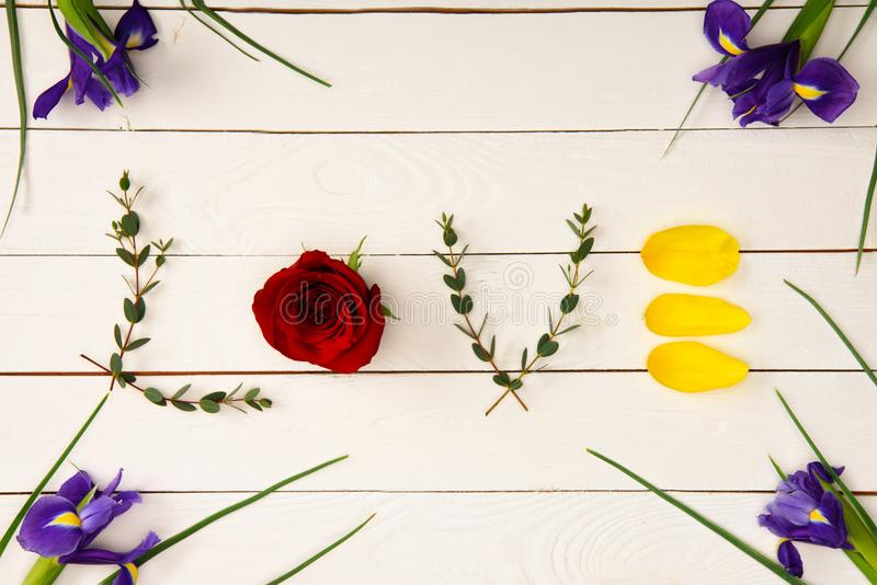 la vista superior del amor de la palabra hecha de elementos florales y del iris hermoso florece imágenes de archivo libres de regalías