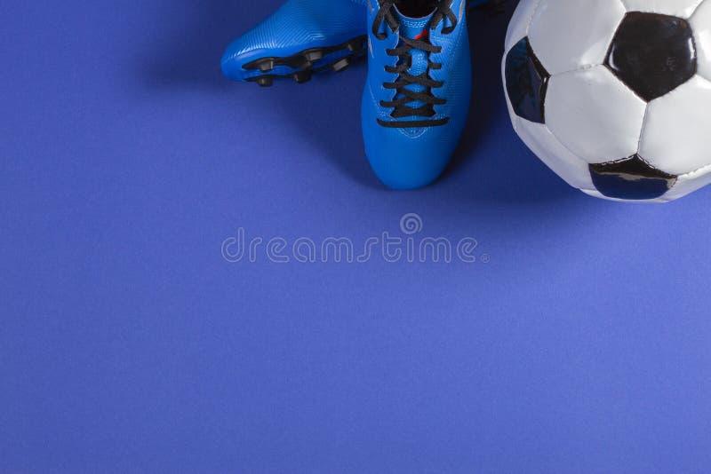 La vista superior del balón de fútbol y de pares de fútbol del fútbol se divierte los zapatos en fondo azul imagenes de archivo