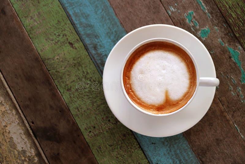 La vista superior del café caliente con arte en forma de corazón del latte en la taza blanca sirvió en la tabla de madera colorea foto de archivo