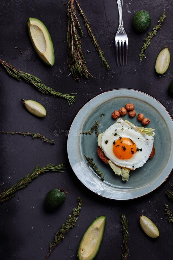 La vista superior del desayuno sano los huevos revueltos con pan y nueces en una placa en fondo negro con el aguacate, romero, ca imagen de archivo