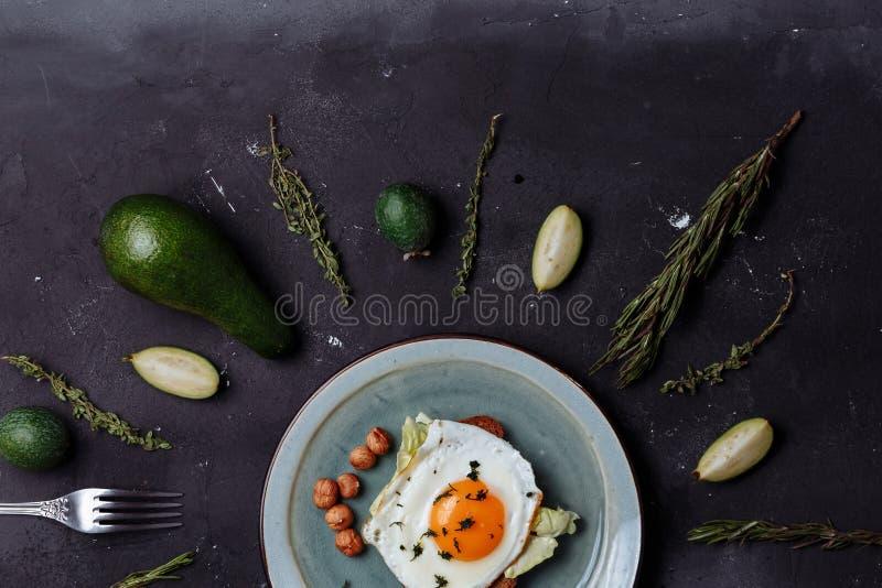 La vista superior del desayuno sano los huevos revueltos con pan y nueces en una placa en fondo negro con el aguacate, romero, ca fotos de archivo libres de regalías