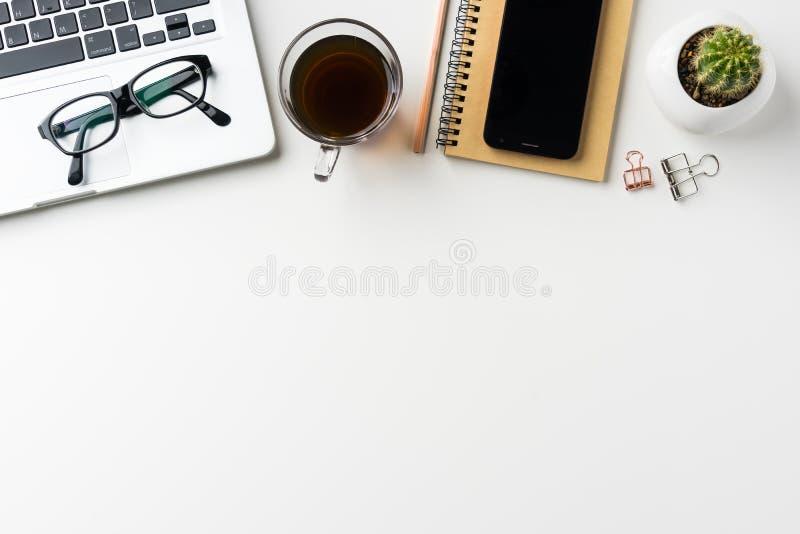 La vista superior del fondo de escritorio blanco con el cuaderno, el teléfono elegante, el cactus y el clip etc para la maqueta d imagenes de archivo