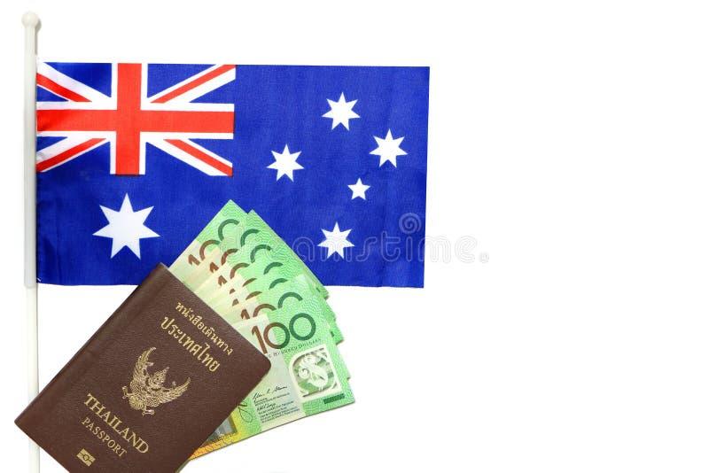 La vista superior del pasaporte de Tailandia tiene dinero australiano del efectivo en su puesta bandera de Australia en el fondo  imagen de archivo libre de regalías