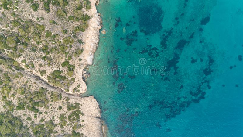 La vista superior a?rea del mar agita golpeando rocas en la playa con la agua de mar de la turquesa Paisaje marino del acantilado fotografía de archivo