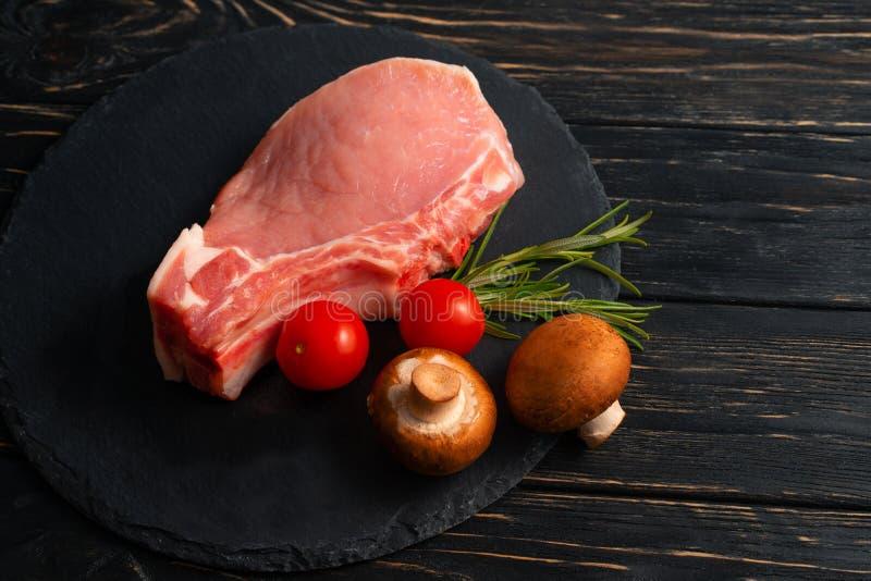 La vista superior a una junta las piezas de los filetes de chuleta de cerdo crudos con las setas del champi??n de los tomates de  fotos de archivo libres de regalías