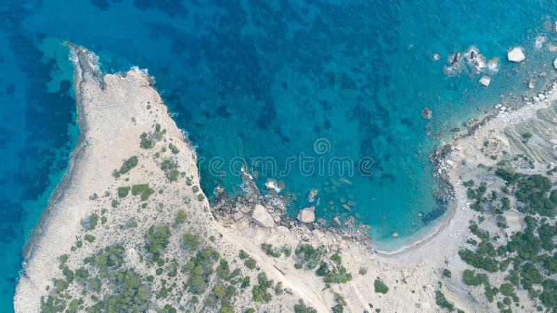 La vista superiore aerea del mare ondeggia colpendo le rocce sulla spiaggia con l'acqua di mare del turchese fotografie stock libere da diritti