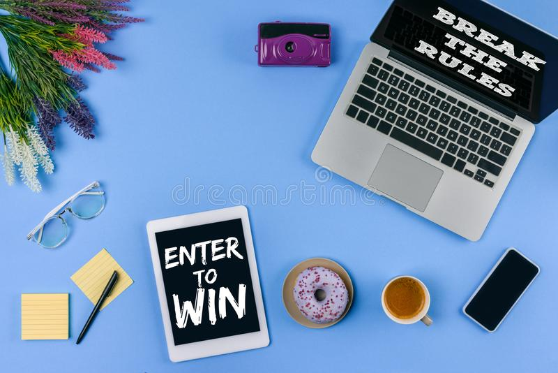 la vista superiore dei dispositivi digitali con le iscrizioni entra per vincere e rompere le regole, i fiori, la tazza di caffè c illustrazione di stock