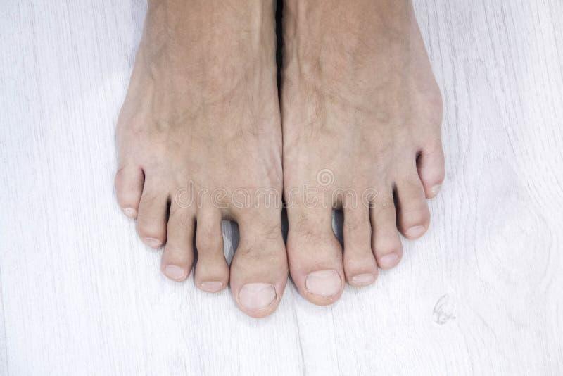 La vista superiore del chiodo maschio ed i piedi su fondo bianco, questo ha un percorso di ritaglio fotografia stock libera da diritti
