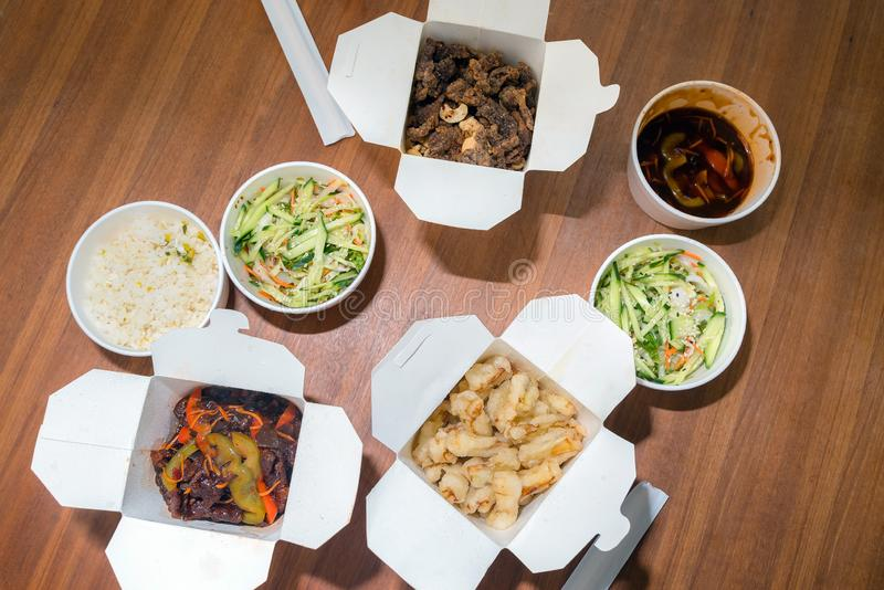 La vista superiore del cinese porta via l'alimento con i bastoni di taglio sulla tavola di legno Alimento asiatico piccante in sc fotografie stock